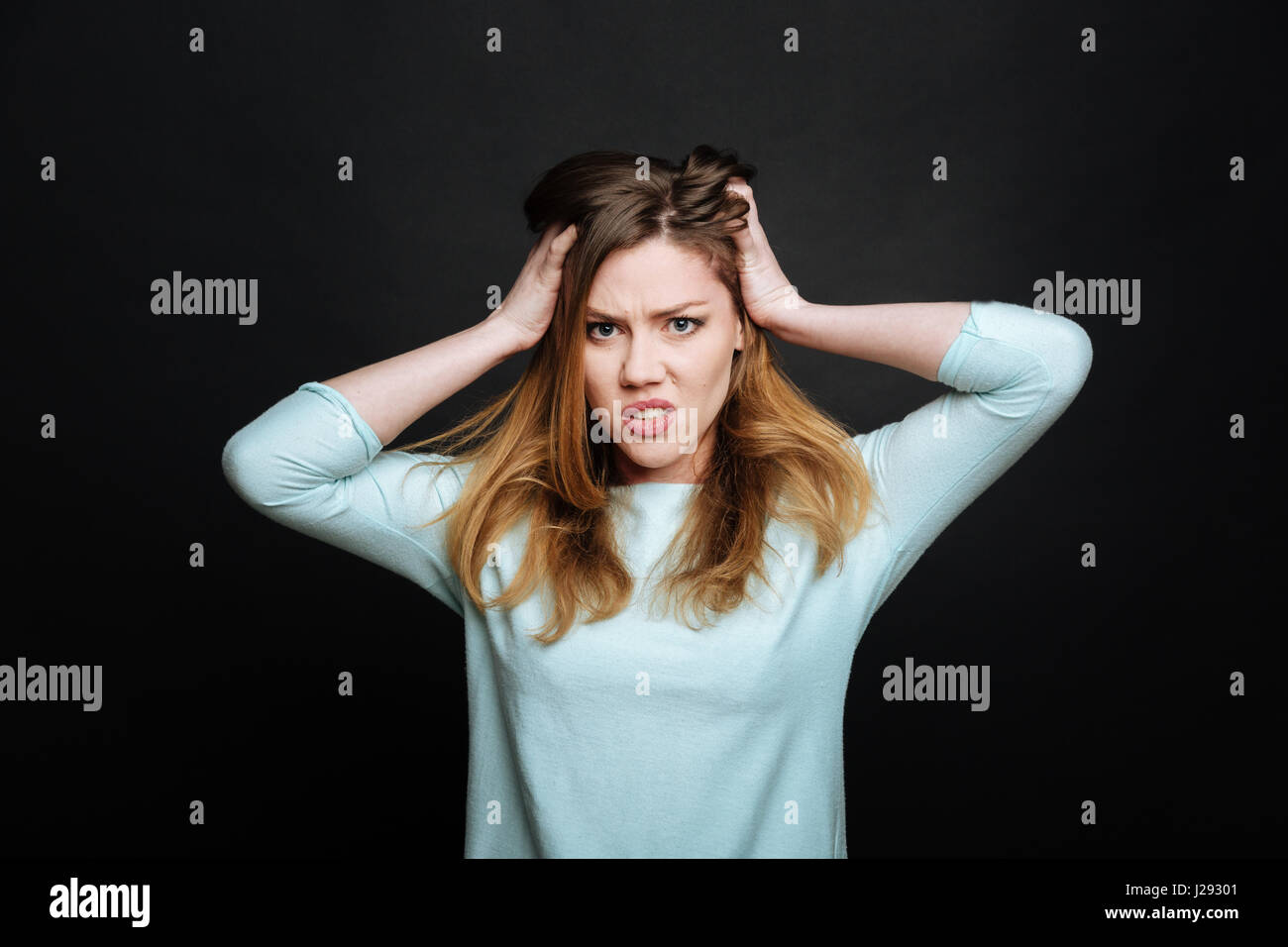 Angry young woman expressing disgust in the black colored studio - Stock Image