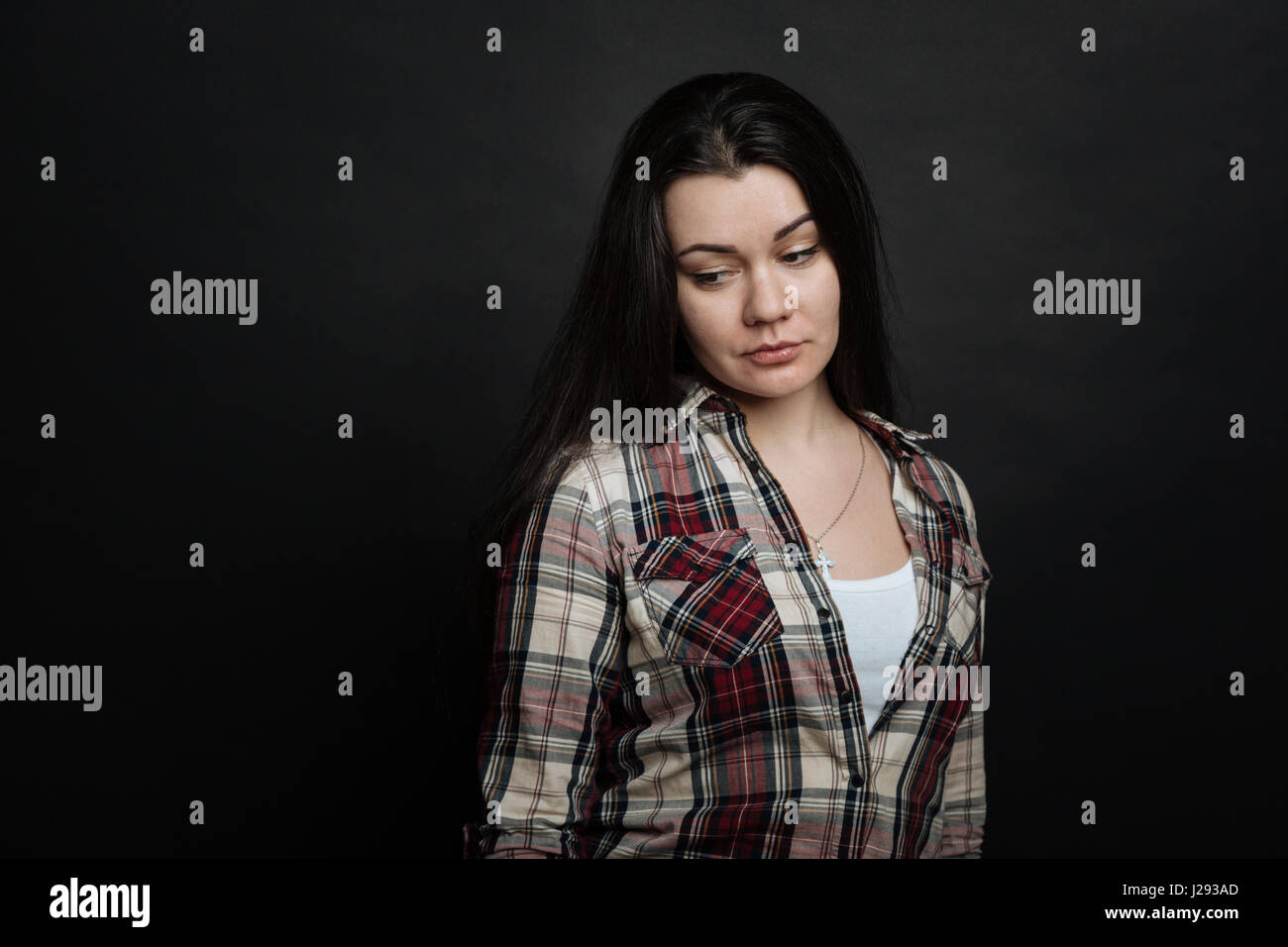 Upset young girl feeling deeply depressed in the studio - Stock Image
