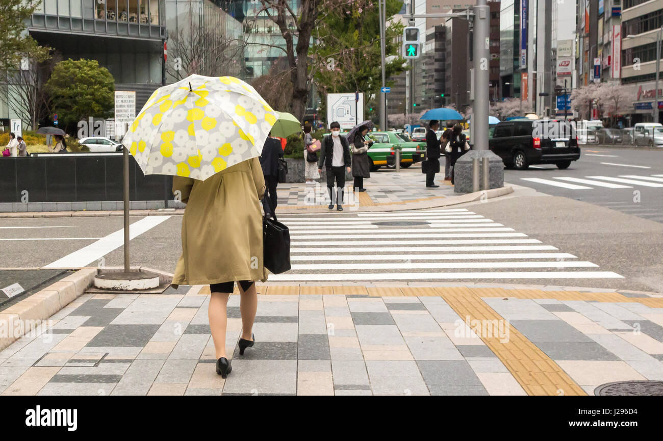 Tokyo, Japan - April 8th, 2017: Woman walking in Tokio wearing trench coat, black bag and umbrella with flower pattern. - Stock Image