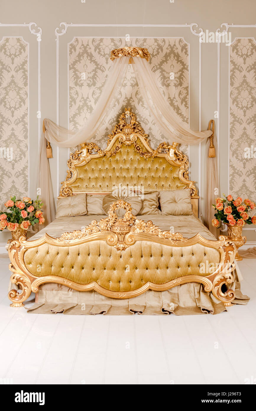 Luxury bedroom in light colors with golden furniture details big comfortable double royal bed in elegant classic interior