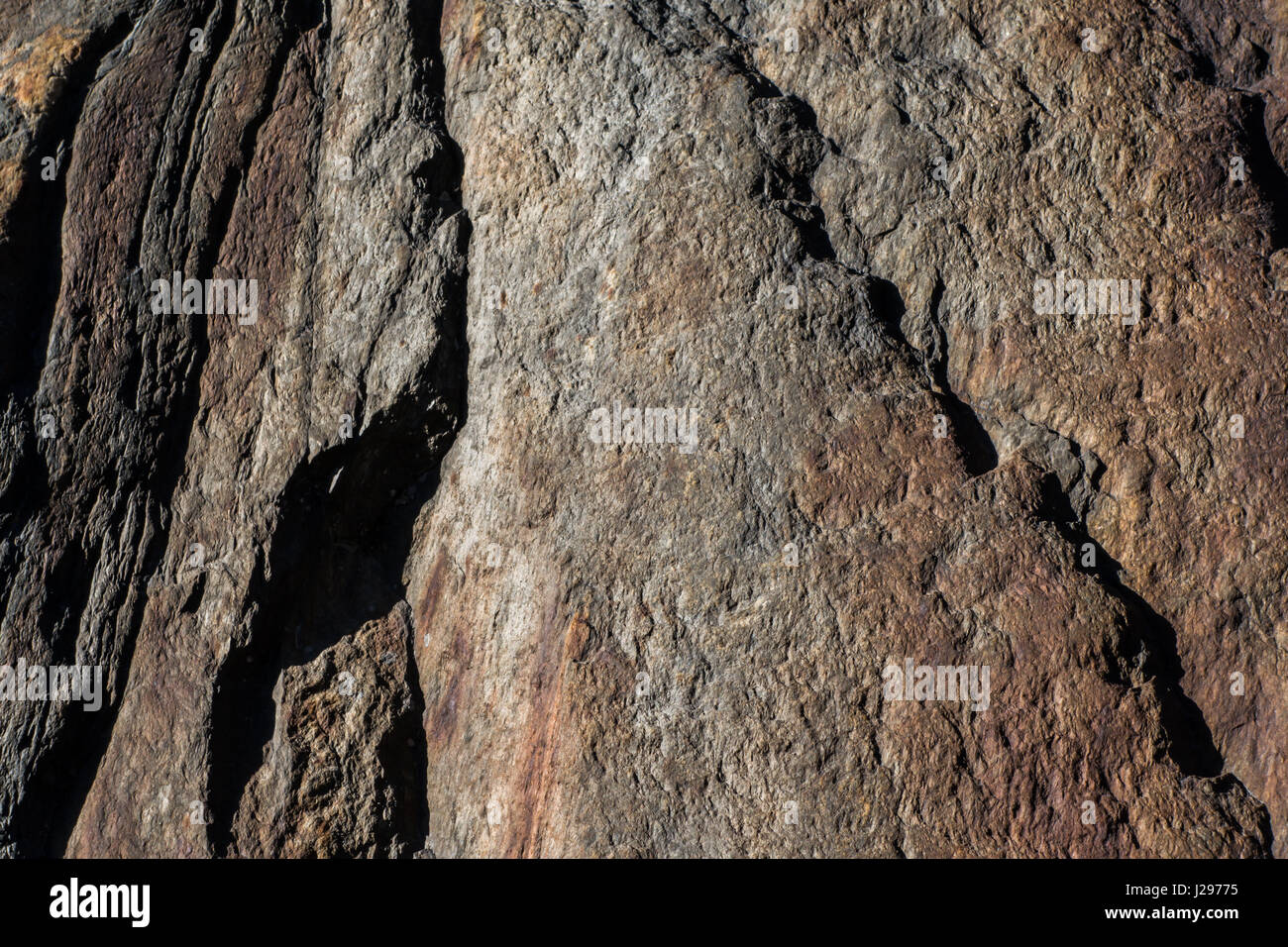 Detail of granite rock with traces of red iron in surface weathered and with signs of erosion Stock Photo