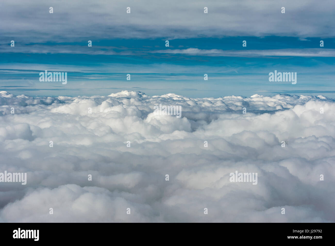 Grey cloud cover hovering low over valley seen from above with blue sky on horizon Stock Photo