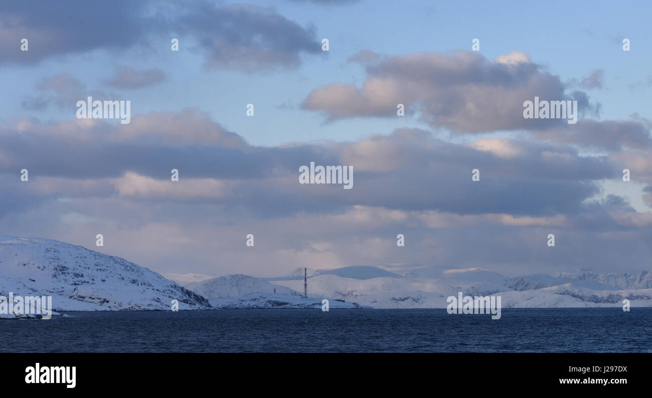 A telecommunications mast stands in a snowy, winter landscape seen from the Hurtigruten route from Hammerfest to - Stock Image