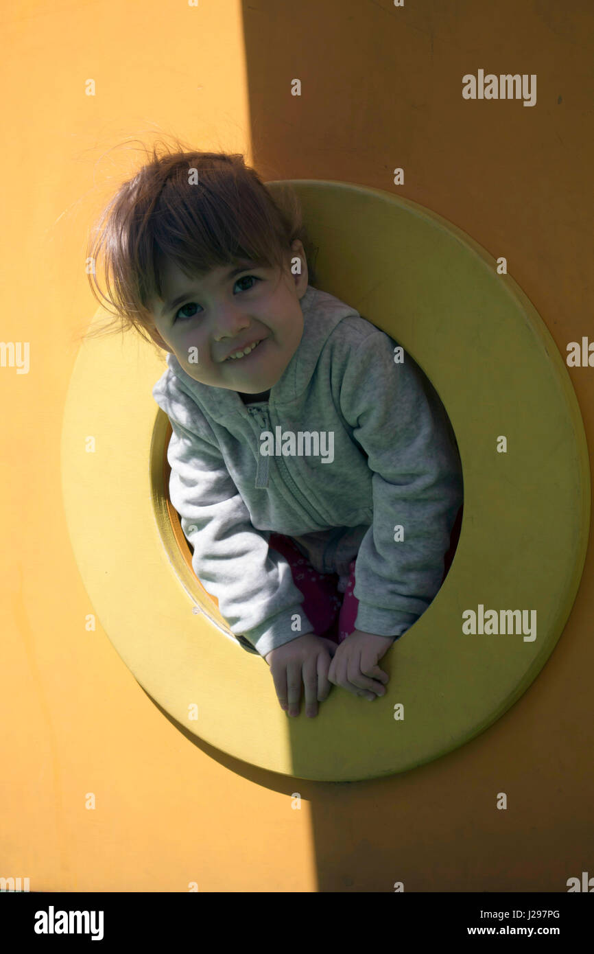 Child enjoys climbing through a tunnel in a children's playground outdoors. - Stock Image
