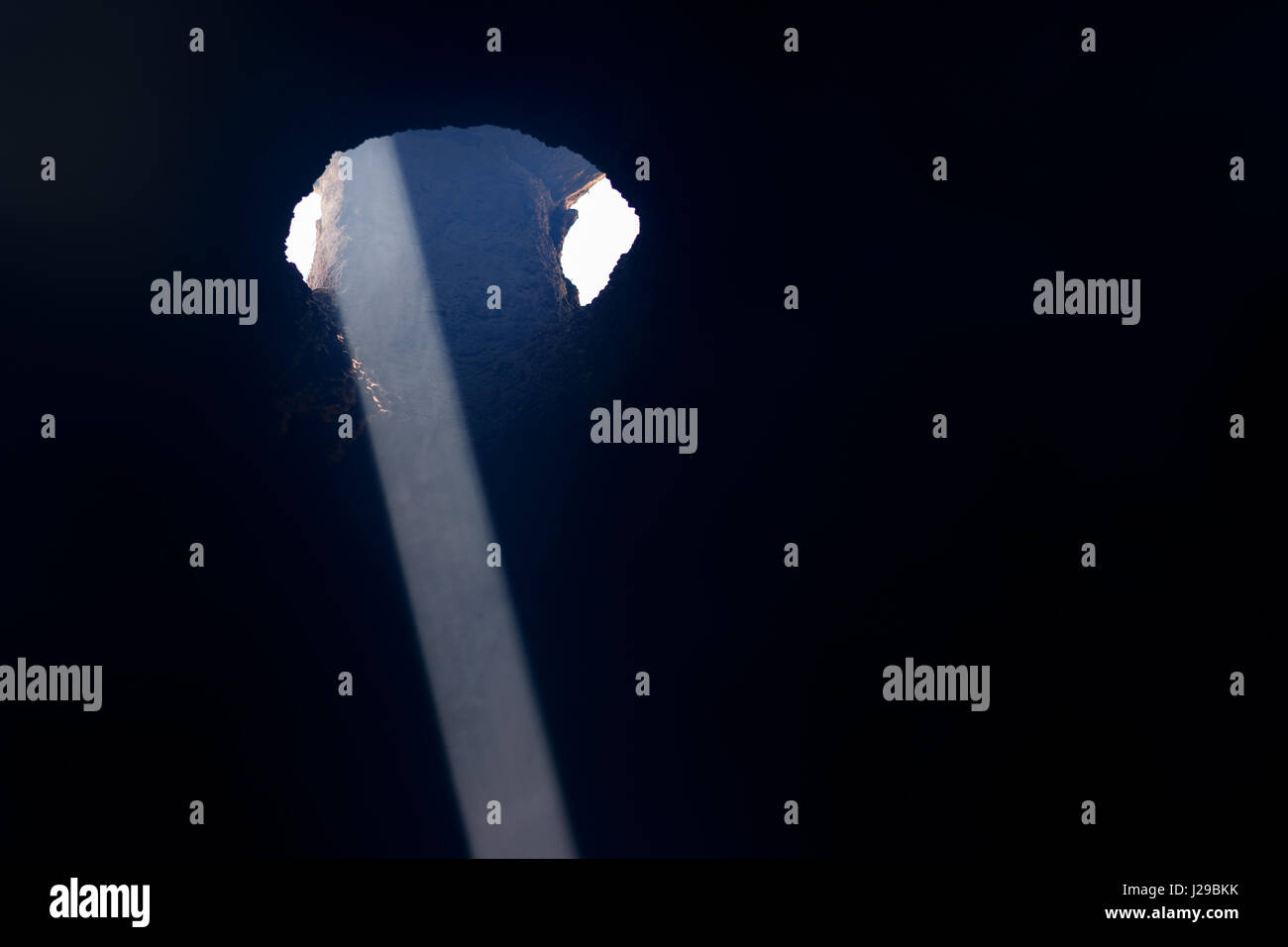 Beam of light from a ceiling opening - Stock Image