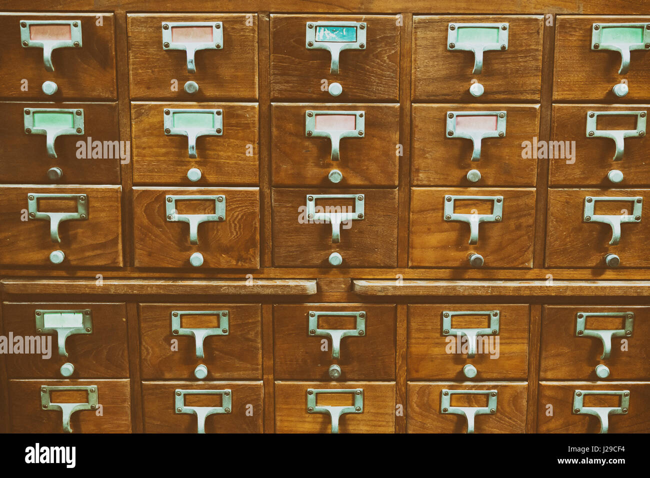 An Old Style Wooden Cabinet Of Library Card Or File Catalog Index Drawers  With Label Holders And Blank Labels Facing Front, Database Concept.