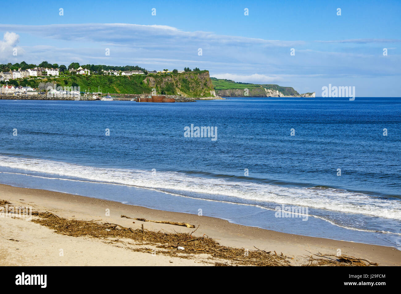 Beach, cliffs, harbor and Atlanic coast at Ballycastle in County Antrim, Northern Ireland, UK, with the far view - Stock Image