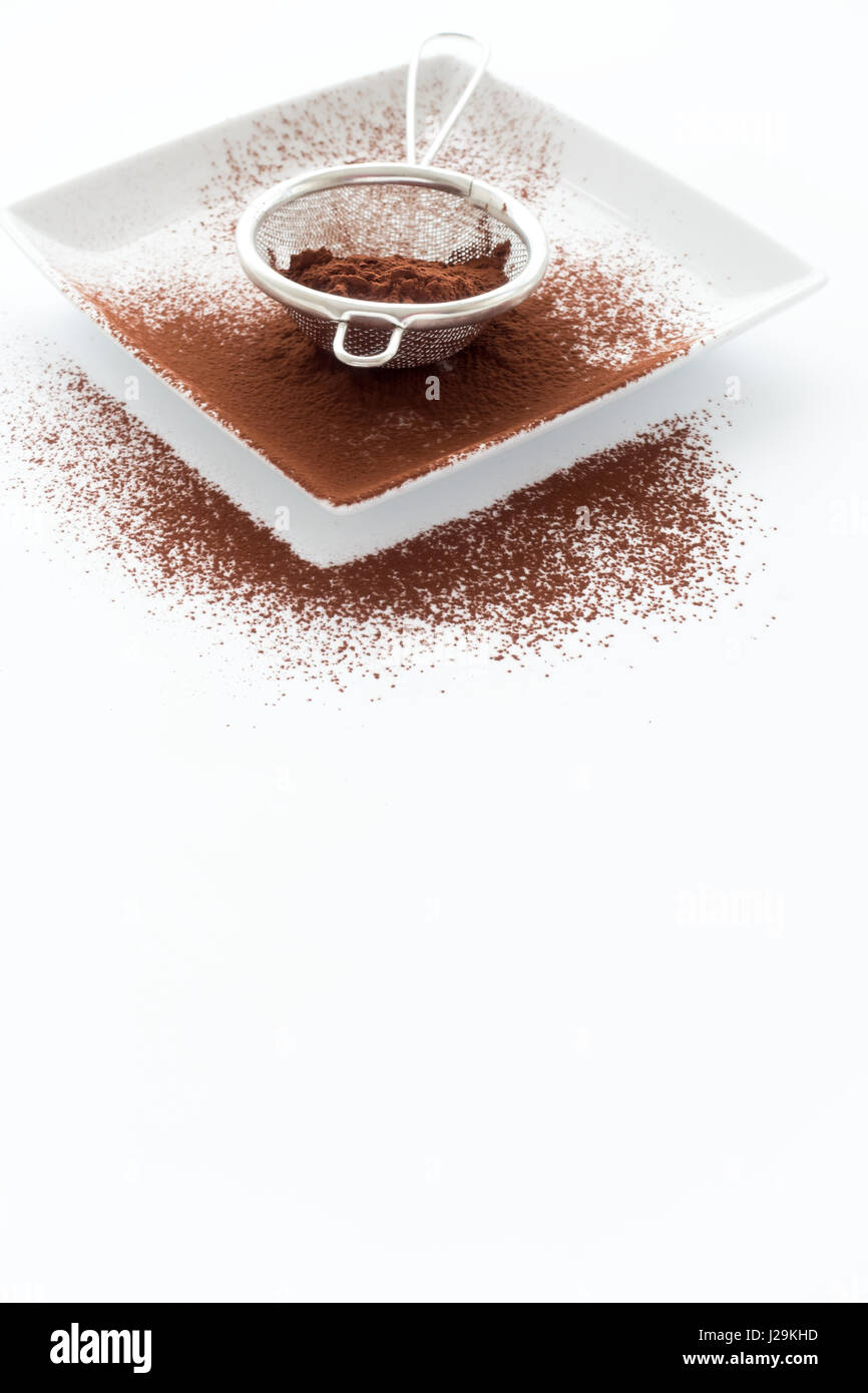 Metal sieve filled with cocoa powder on white square porcelain plate on white background with lots of copy space - Stock Image