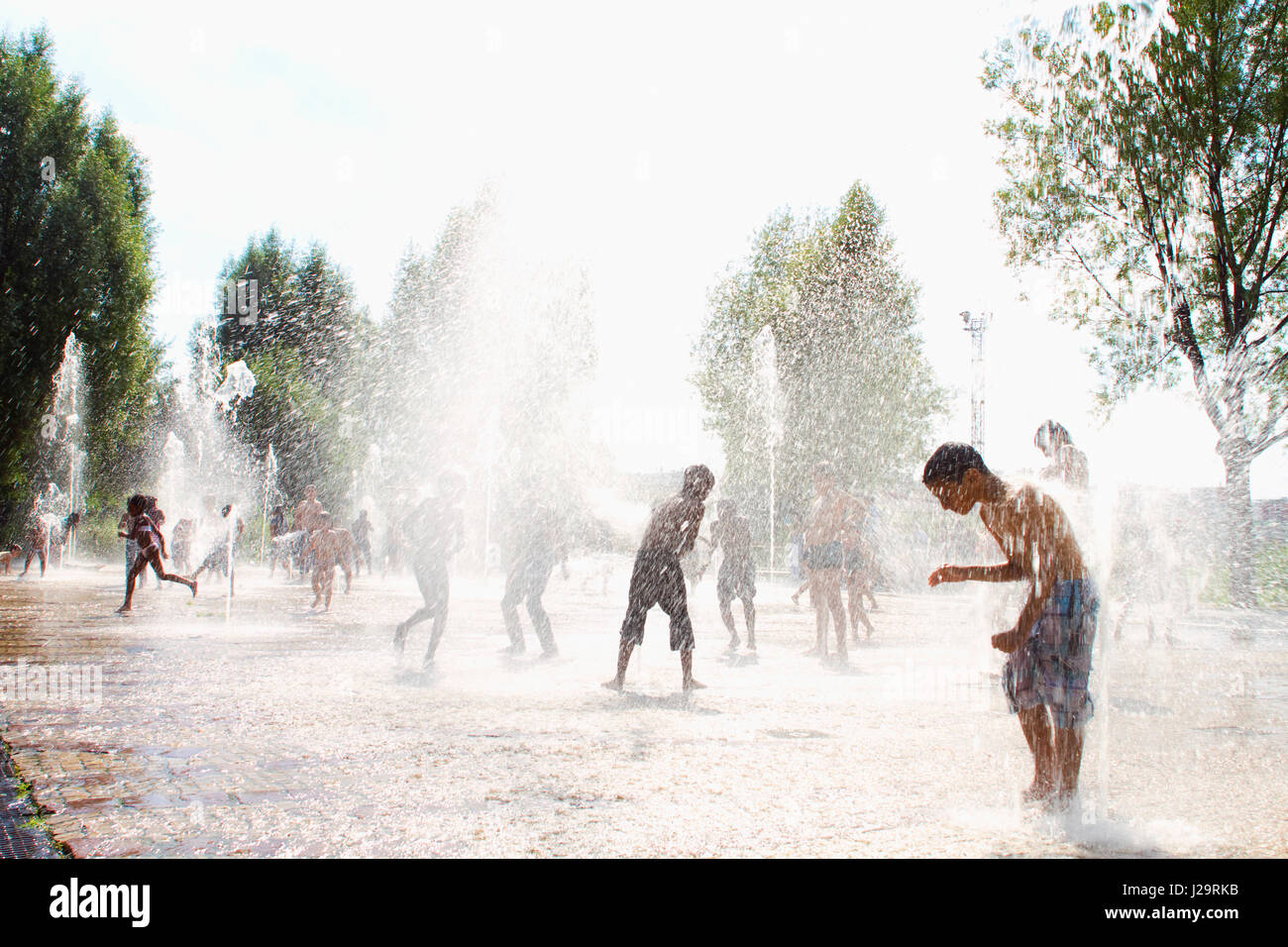 France, Paris, 17th district, Parc Clichy-Batignolles Martin Luther King, children playing with water jets in summer - Stock Image
