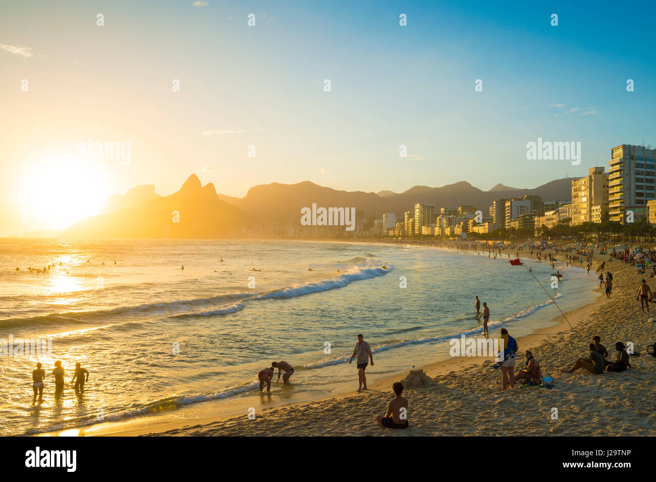 RIO DE JANEIRO - FEBRUARY 14, 2017: Visitors gather at the Arpoador end of Ipanema Beach to watch the sun set behind Stock Photo