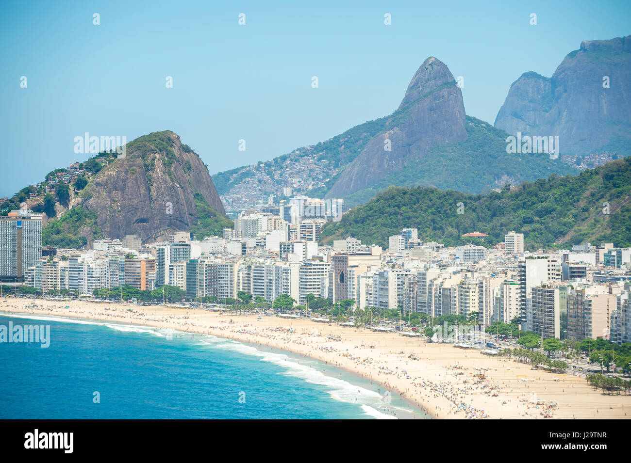 Bright scenic view of the broad crescent of Copacabana Beach with the dramatic skyline of Rio de Janeiro, Brazil - Stock Image