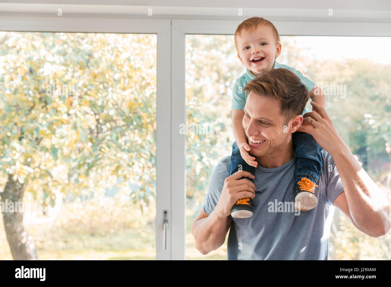 Toddler boy on father's shoulders at home by window - Stock Image