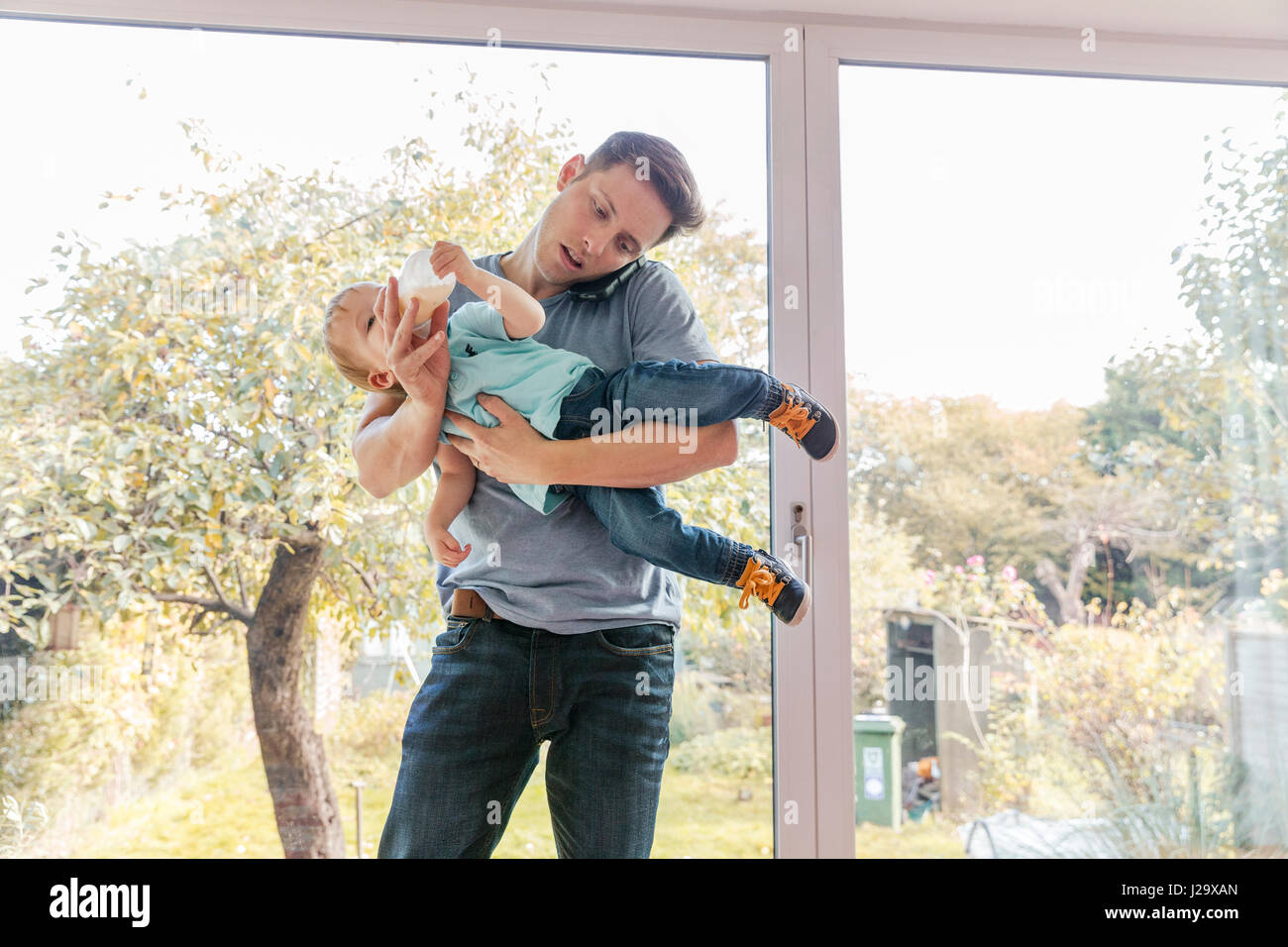 Father holding toddler son while on phone at home, by window - Stock Image