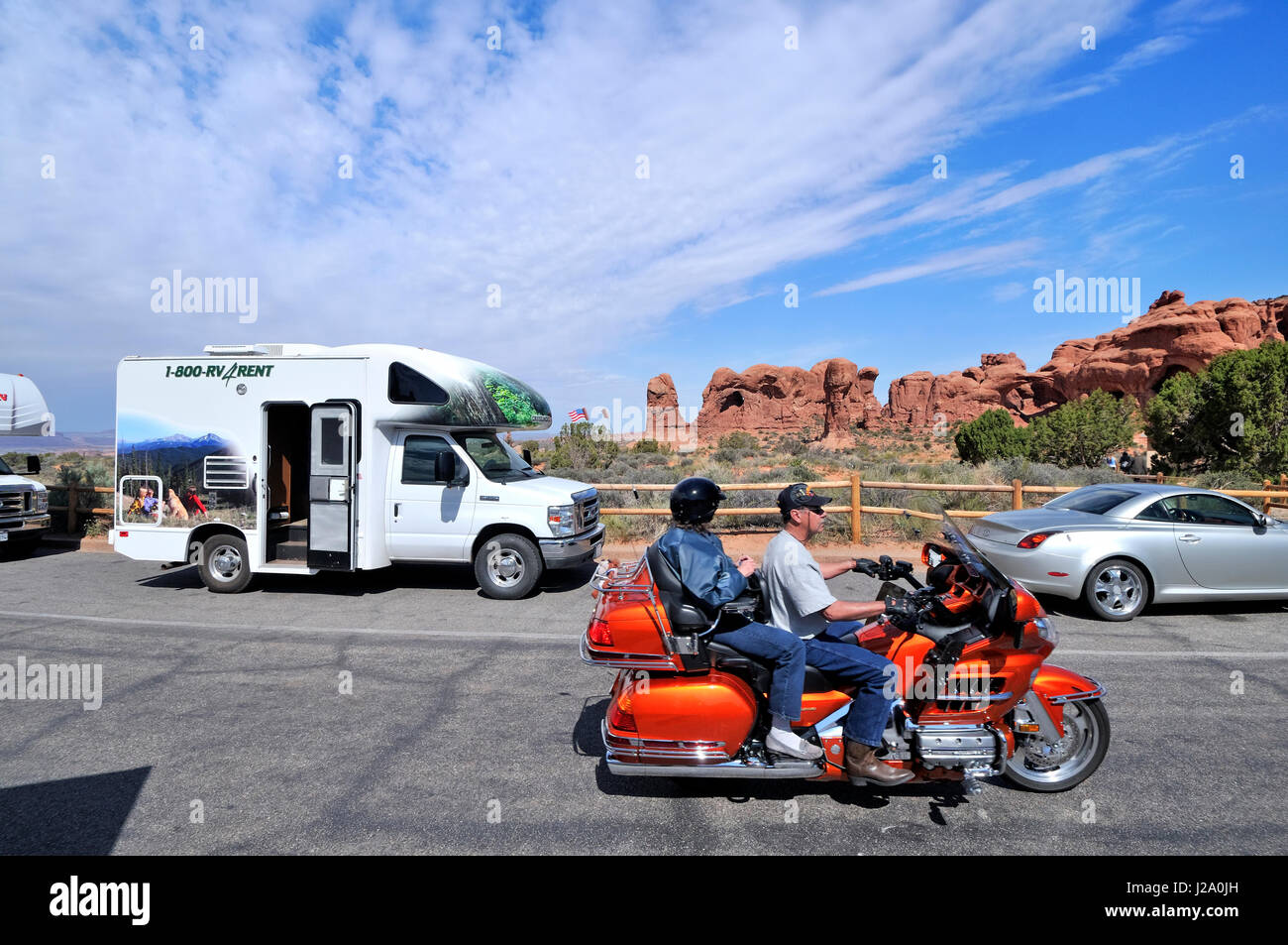 A rented camper and a comfortable motorbike on a parking lot in Arches National Park - Stock Image