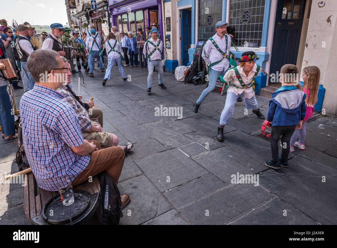 Adults and children enjoy the the Morris Dancing outside the Dolphin Pub on The Barbican in Plymouth on a warm spring - Stock Image