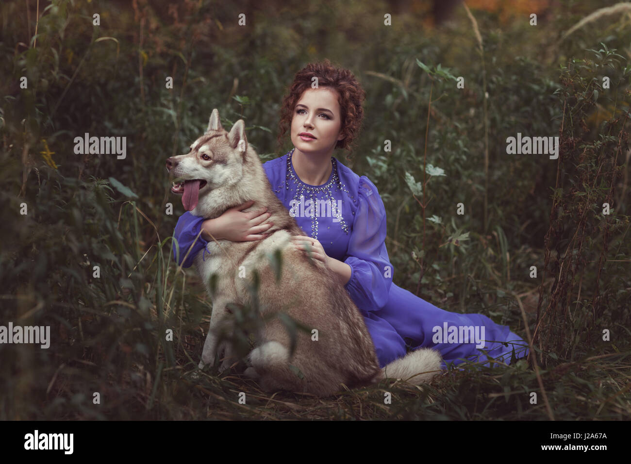 Girl hugging husky dog, they are in a fairy tale. - Stock Image