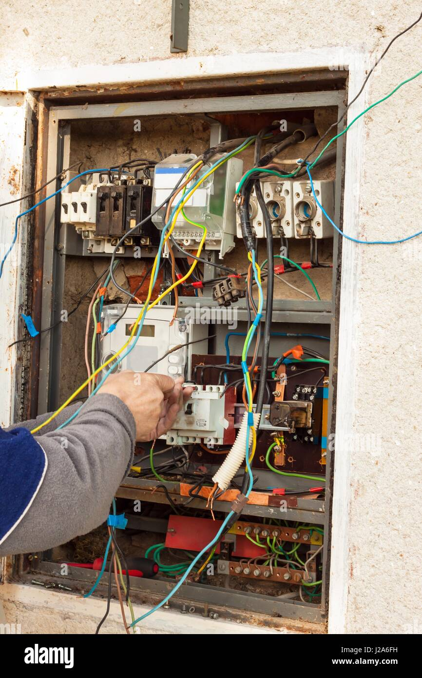 Repair of electricity distribution in an old house. The man repairs ...