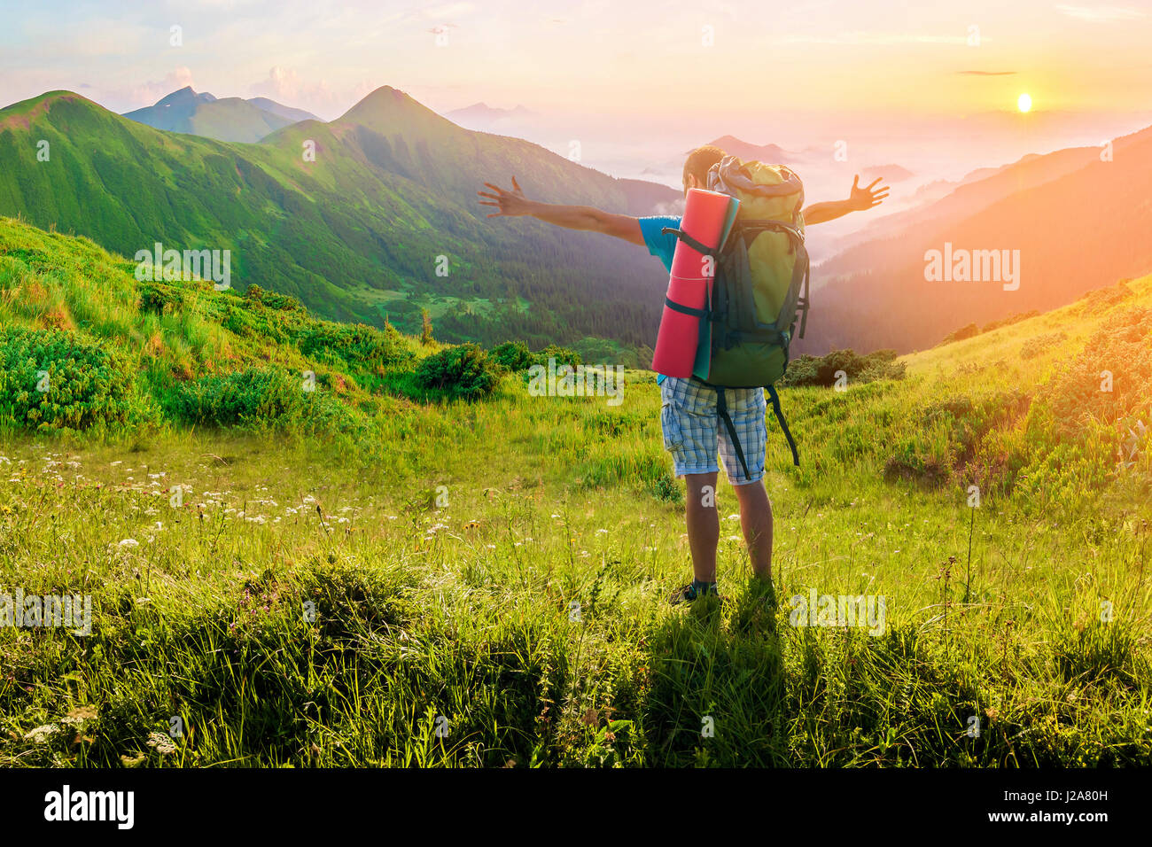 Hiker with a backpack standing in mountains. Amazing nature landscape. Soft light effect Stock Photo