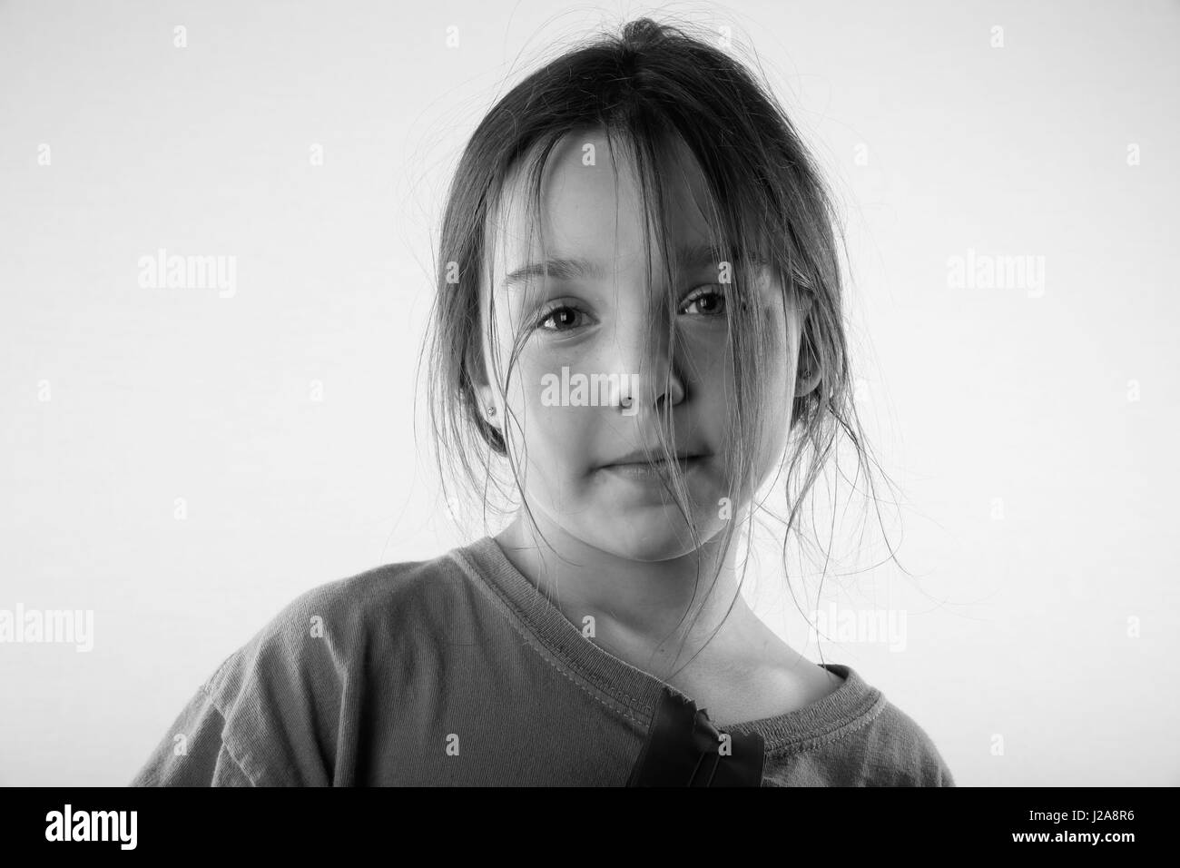 A 9 year old girl looking serious on white background. - Stock Image