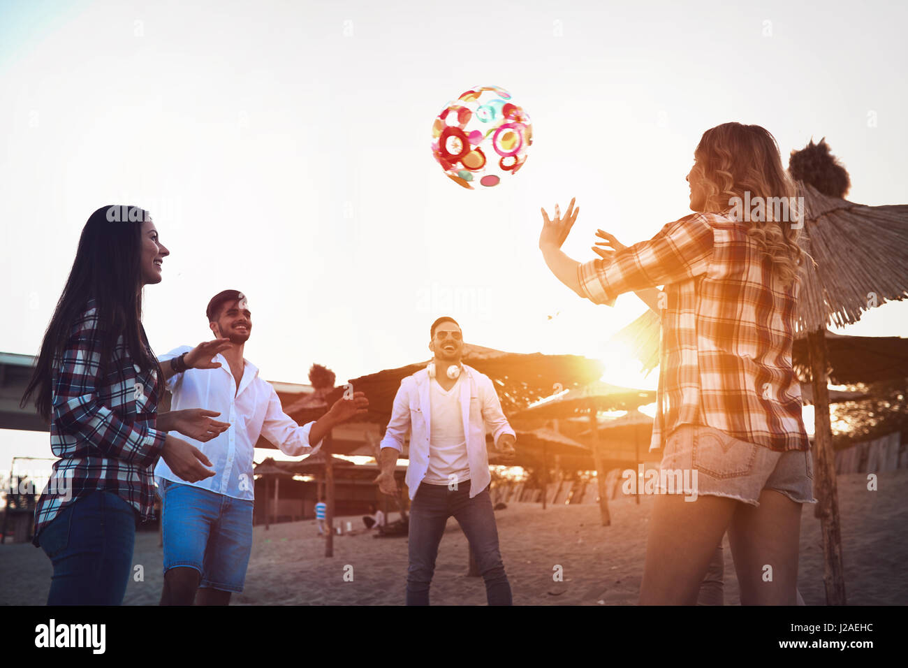 Group of happy young people playing with ball on beach in summer - Stock Image