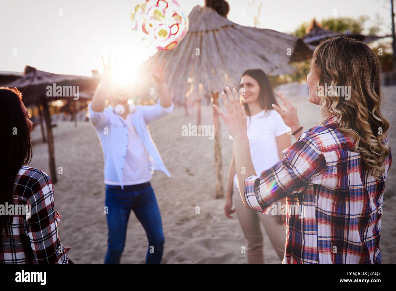 Group of happy young people enjoying summer vacation on beach - Stock Image