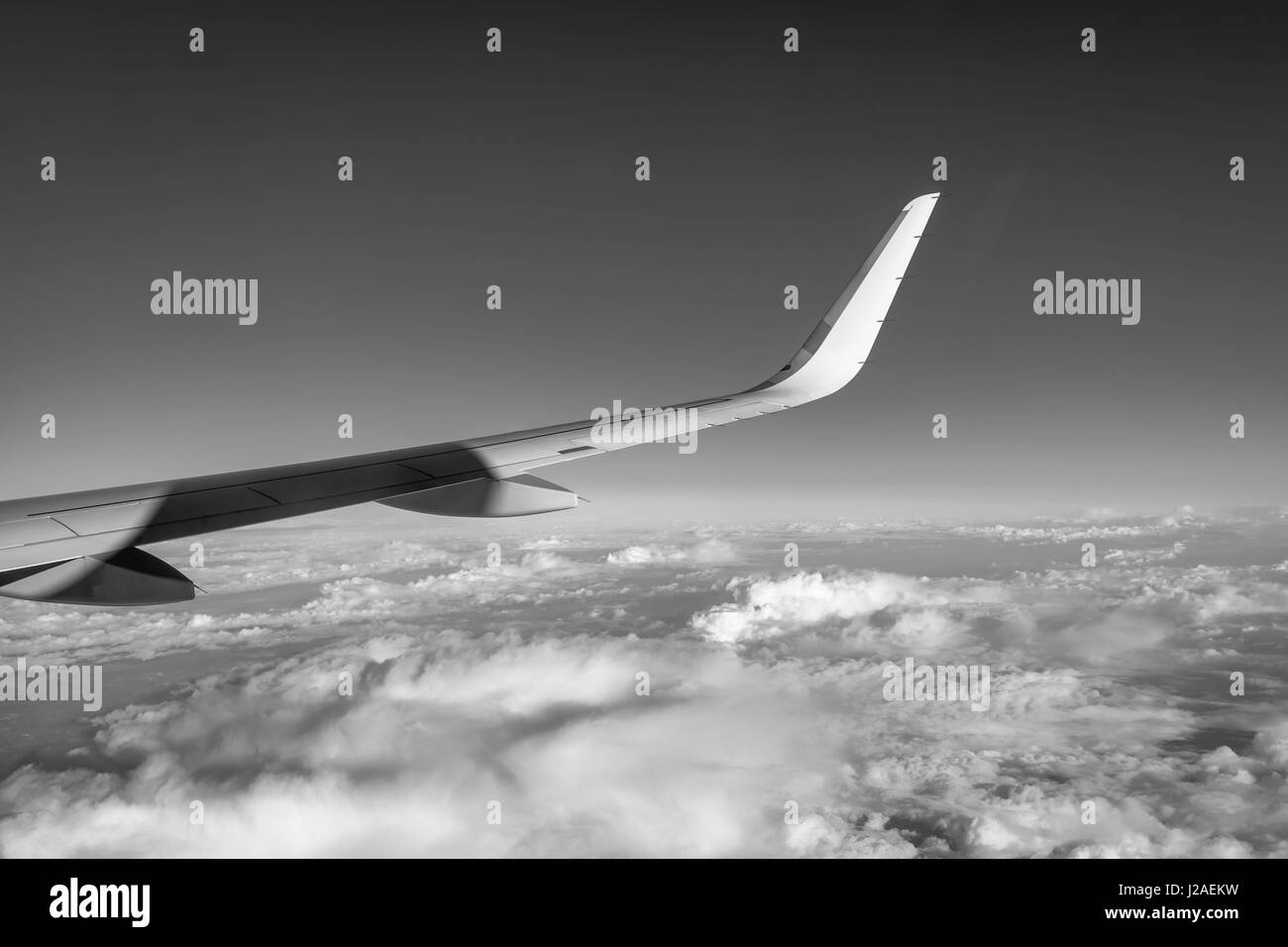 Airplane flying high above the clouds (black and white photography) - Stock Image