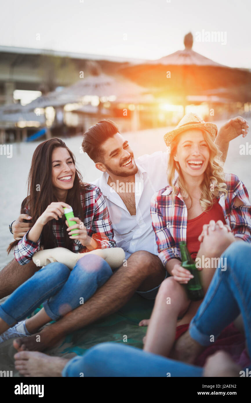 Happy friends partying and having fun on beach at summer - Stock Image