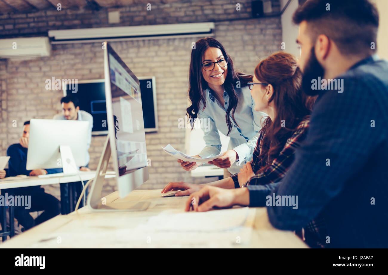Happy creative coworkers working in designer office - Stock Image