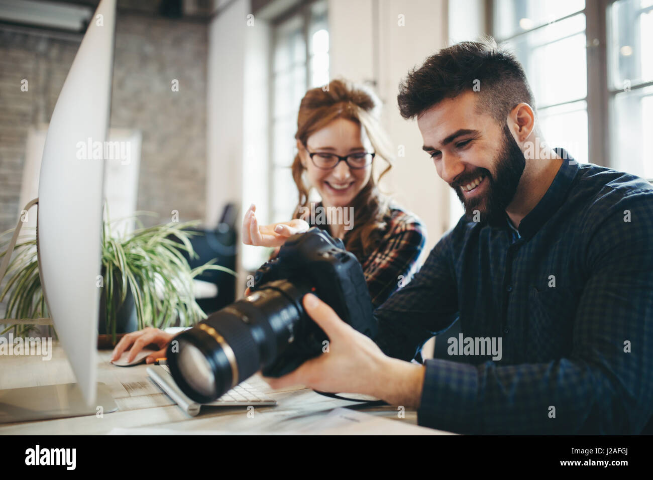 Company photo editor and photographer working together in office - Stock Image