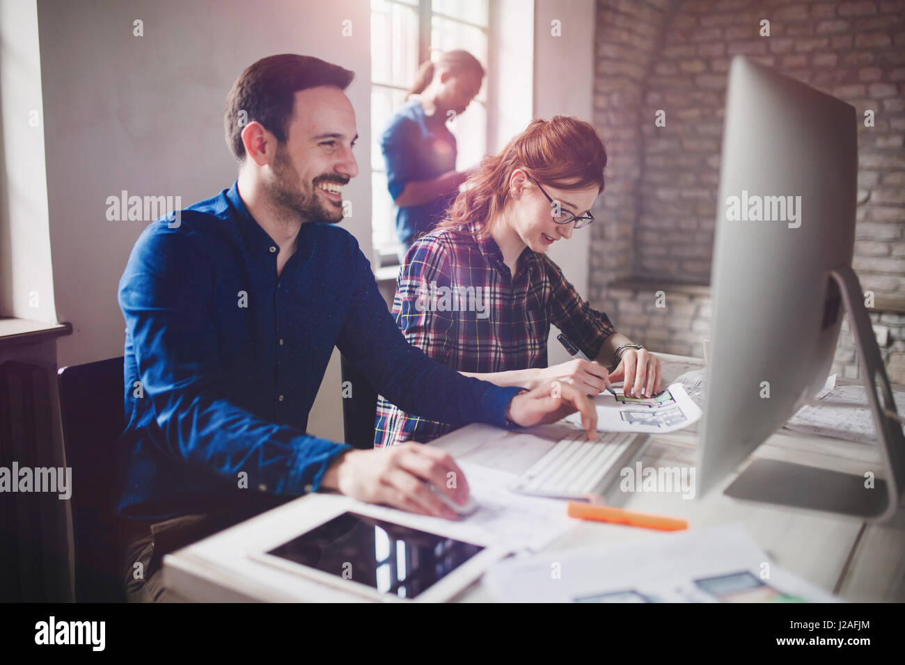 Coworking and corporate colleagues working in designer architect office - Stock Image