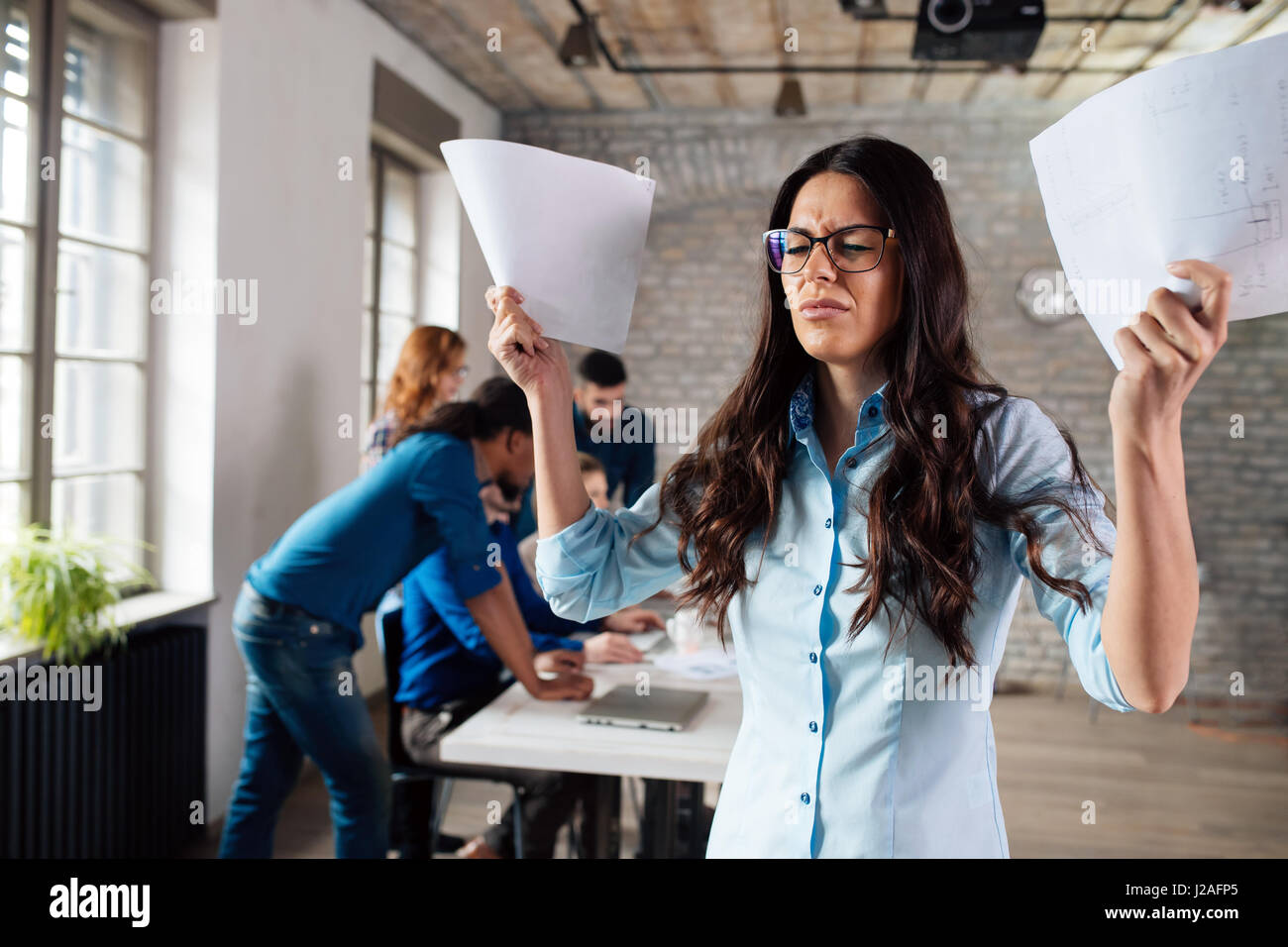 Overworked stressful businesswoman overwhelmed with papers in office - Stock Image