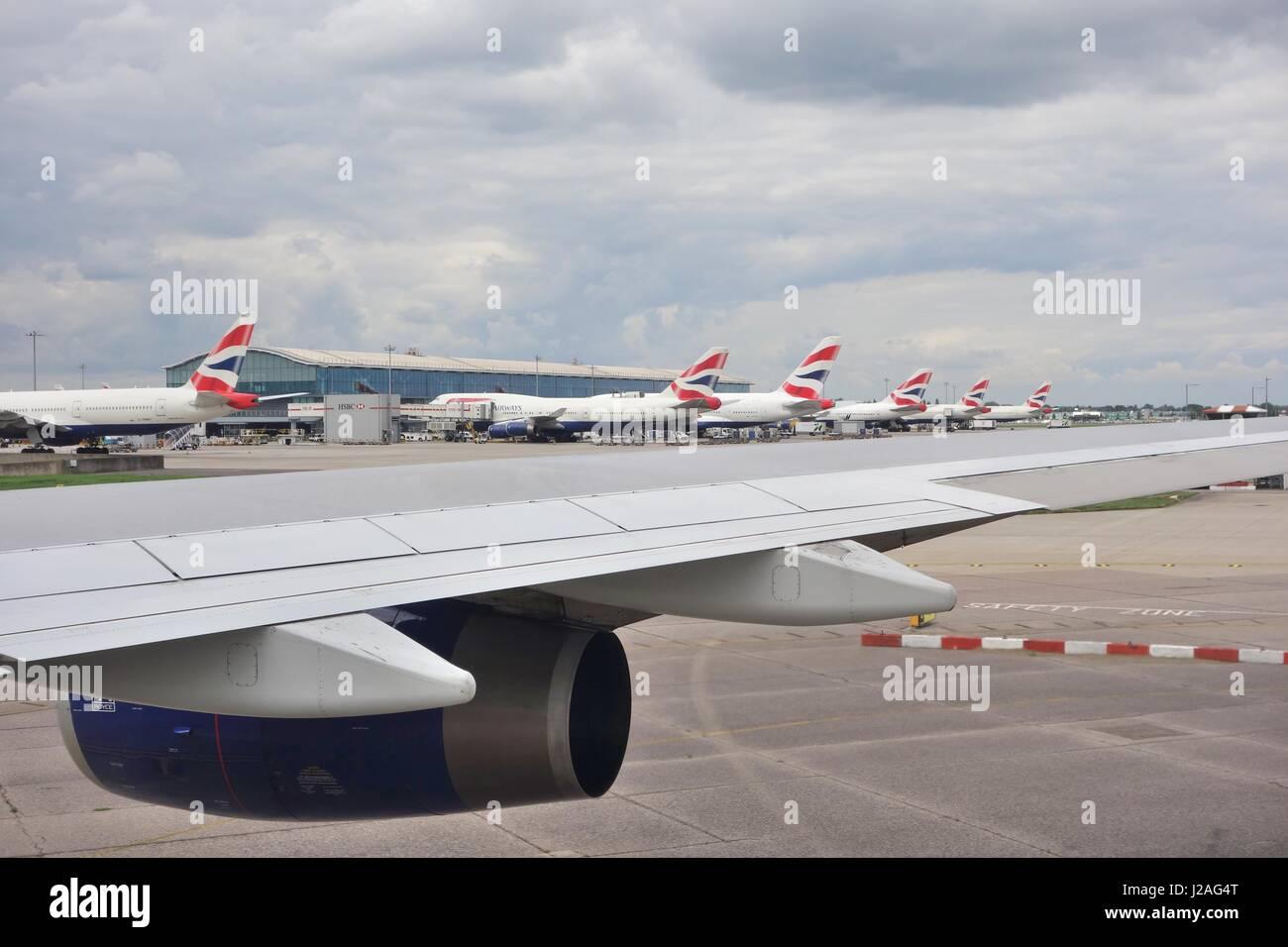 A row of British Airways aircraft sitting at Heathrow airport, England, UK - Stock Image