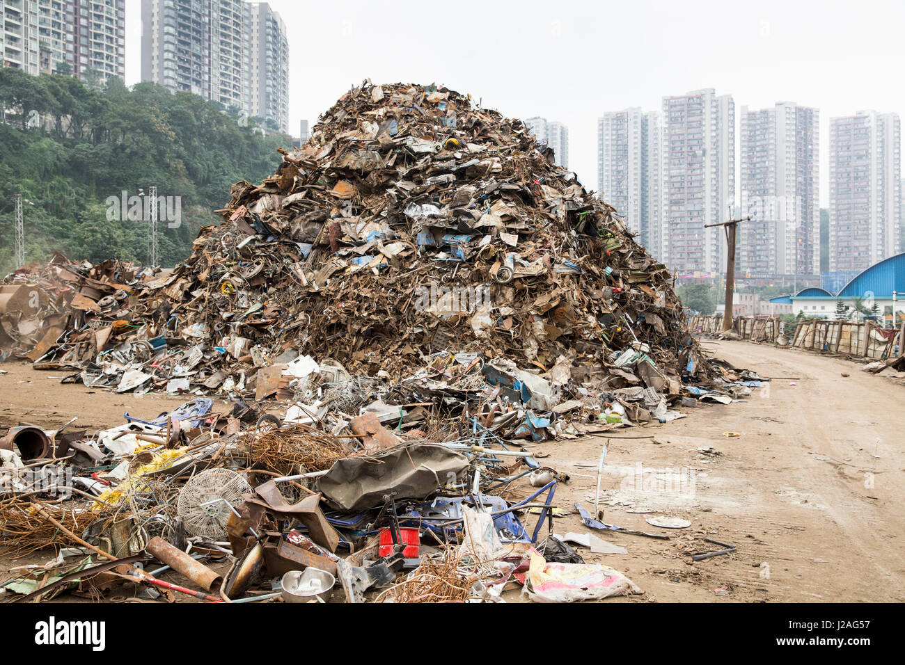China, Chongqing, Massive pile of garbage and scrap metal outside cargo railroad terminal along Yangtze River - Stock Image