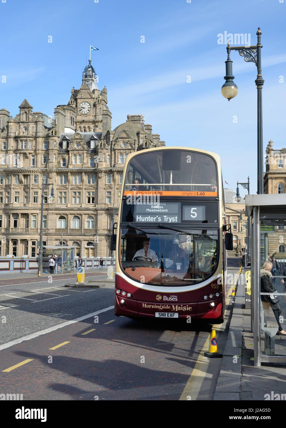 An Edinburgh double decker bus crossing North Bridge with the Balmoral Hotel to the rear in Scotland, UK - Stock Image