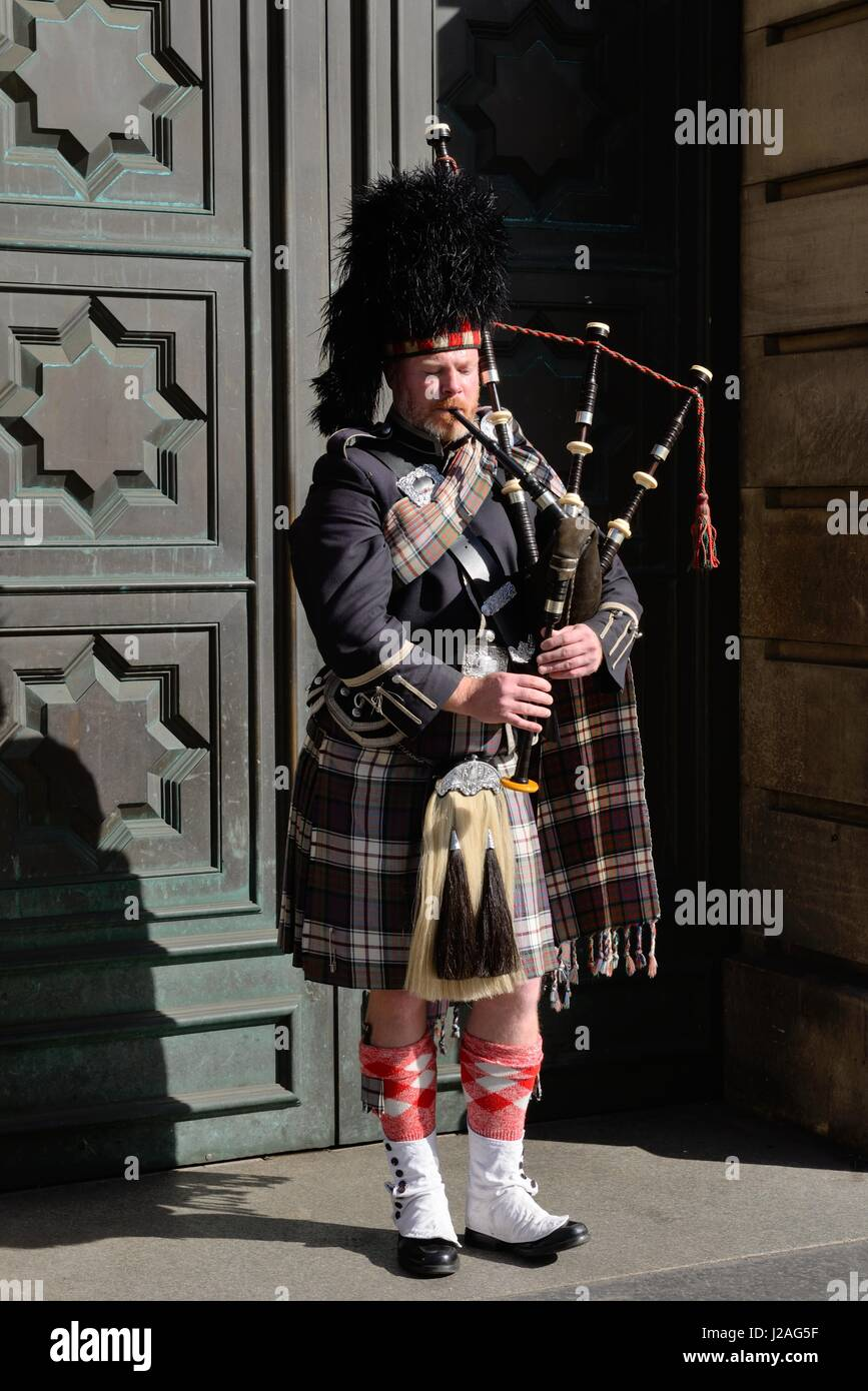 A lone piper in full Scottish regalia busks on the Royal Mile, Edinburgh, Scotland, UK Stock Photo