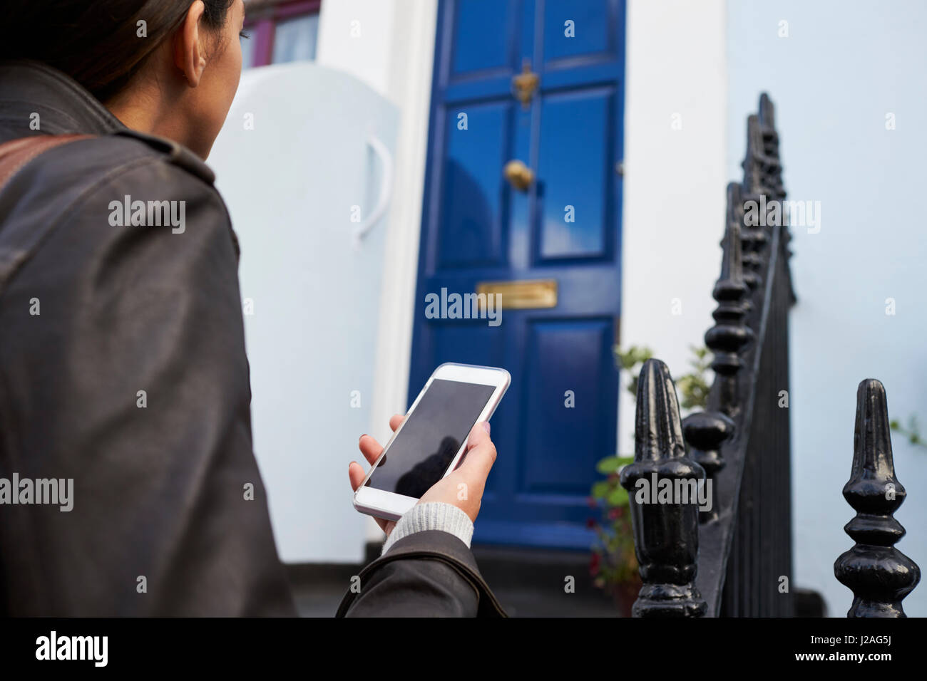 Young woman arriving at London house she's booked to stay in - Stock Image