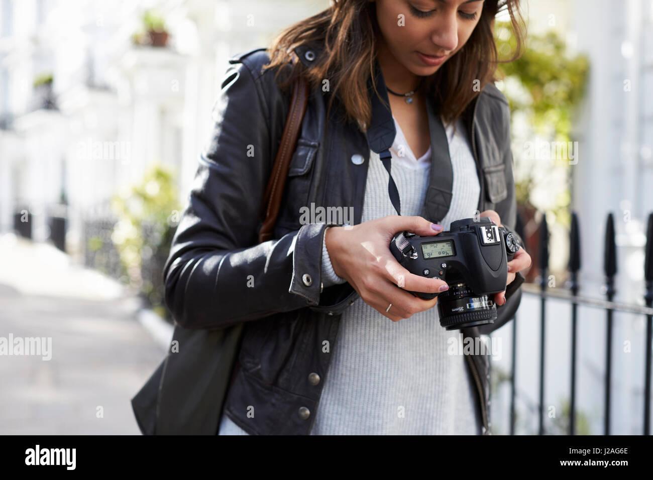 Woman looking at the screen of a digital camera, close up - Stock Image