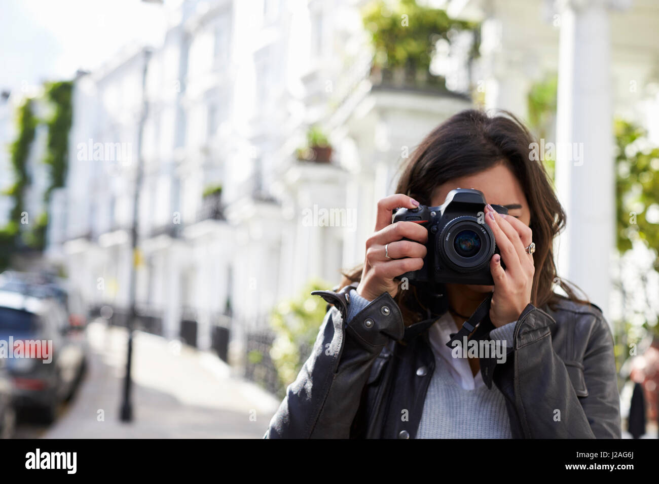 Young woman in street taking photo with SLR camera, close up - Stock Image