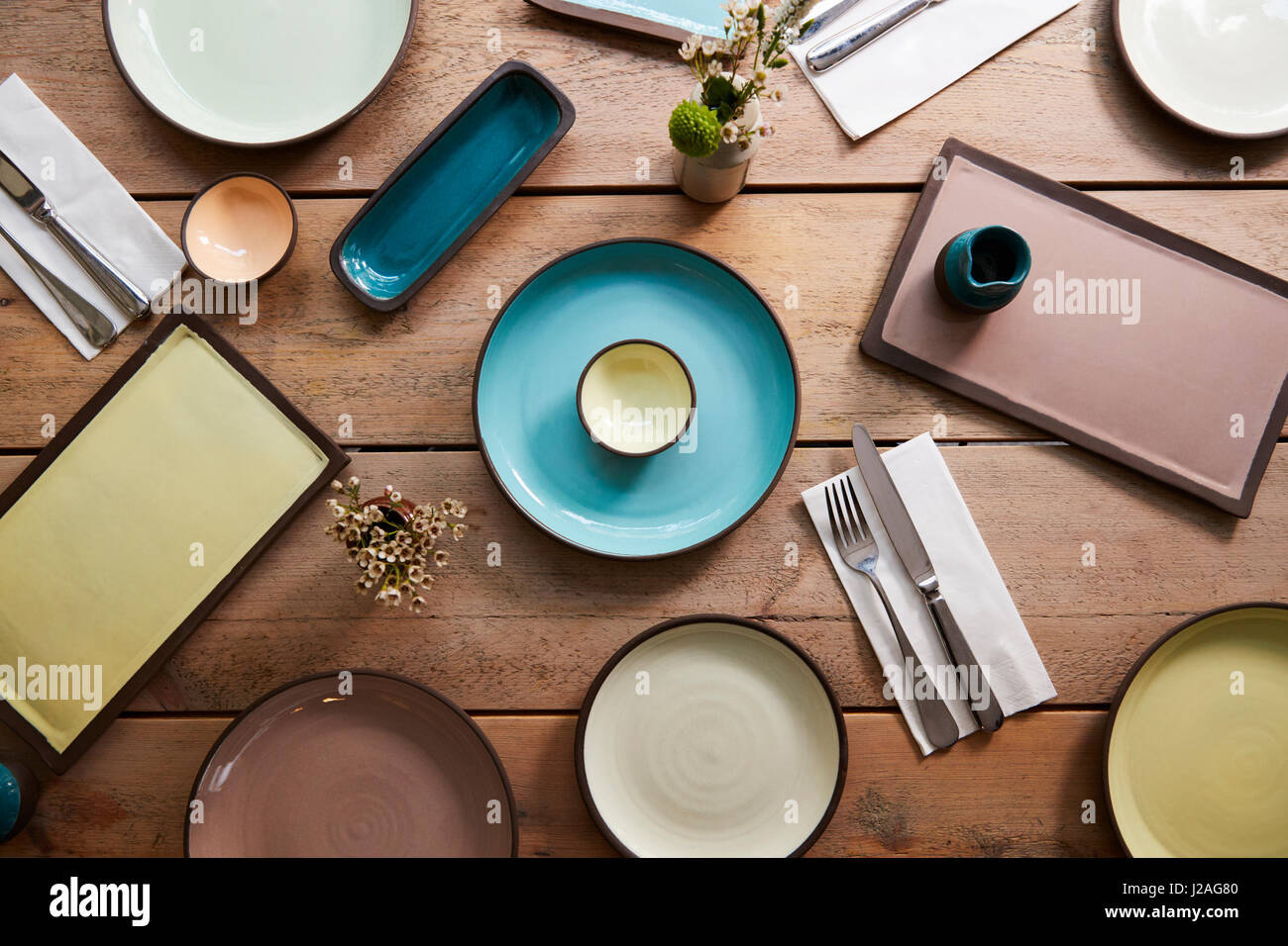 Handmade earthenware and cutlery on a table, overhead shot - Stock Image