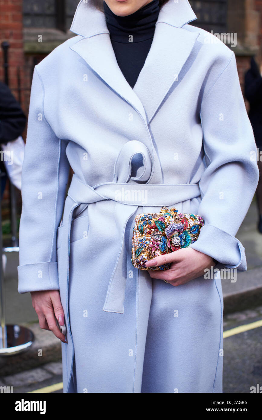LONDON - FEBRUARY, 2017: Mid section of woman wearing belted overcoat, holding small appliqué decorated clutch - Stock Image