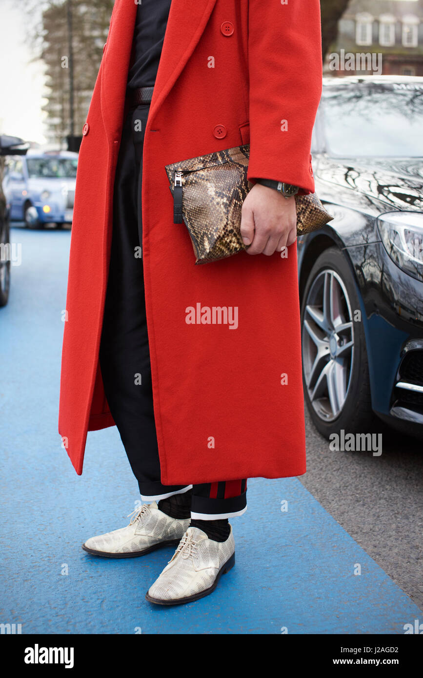 LONDON - FEBRUARY, 2017: Low section of man standing in street wearing red overcoat holding a snakeskin bag outside - Stock Image