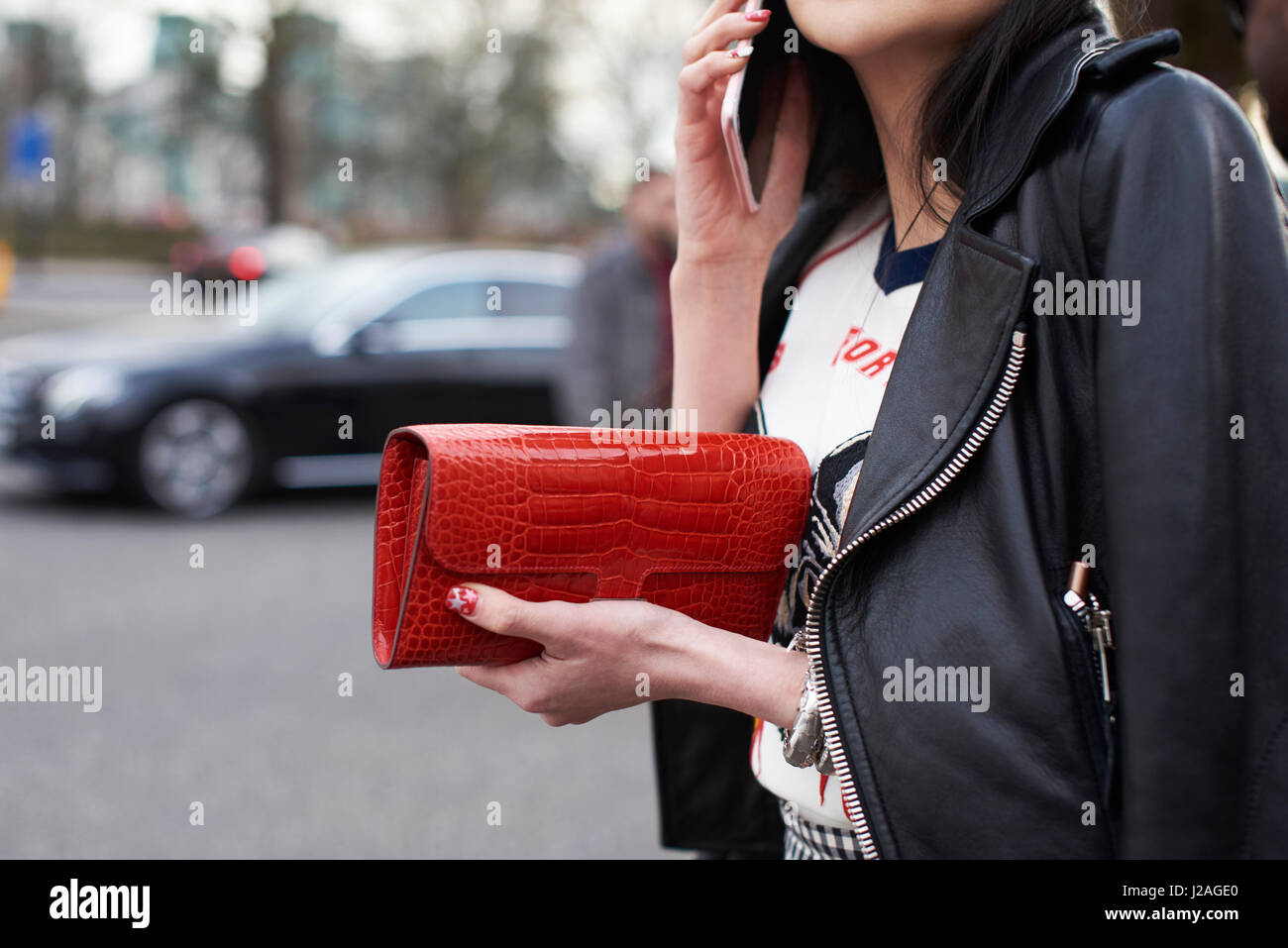 LONDON - FEBRUARY, 2017: Mid section close up of woman wearing a black leather bike jacket, holding a red Hermes - Stock Image