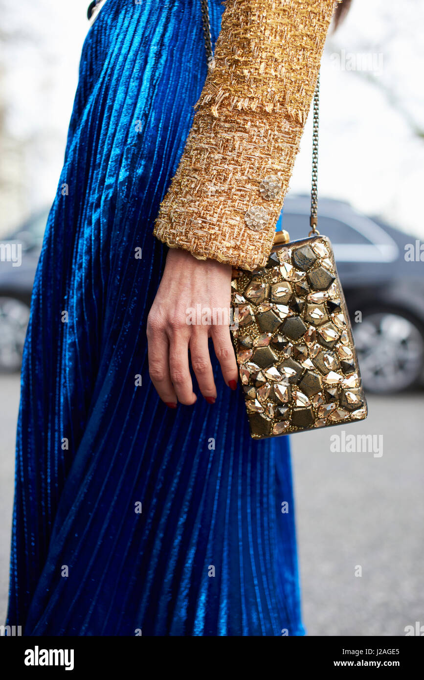 LONDON - FEBRUARY, 2017: Mid section of woman wearing a long blue pleated skirt and a small embellished shoulder - Stock Image