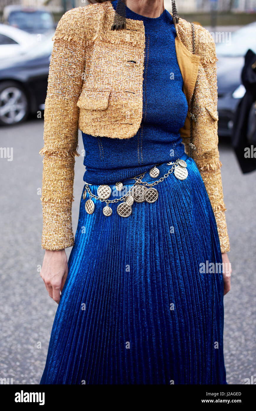 LONDON - FEBRUARY, 2017: Mid section of woman wearing a short wool jacket, long blue pleated skirt and a Chanel - Stock Image