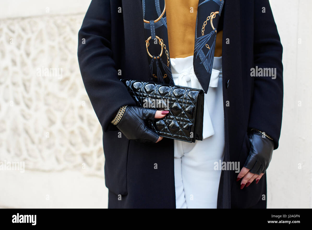 LONDON - FEBRUARY, 2017: Mid section of woman in overcoat and fingerless gloves holding a Chanel clutch handbag - Stock Image