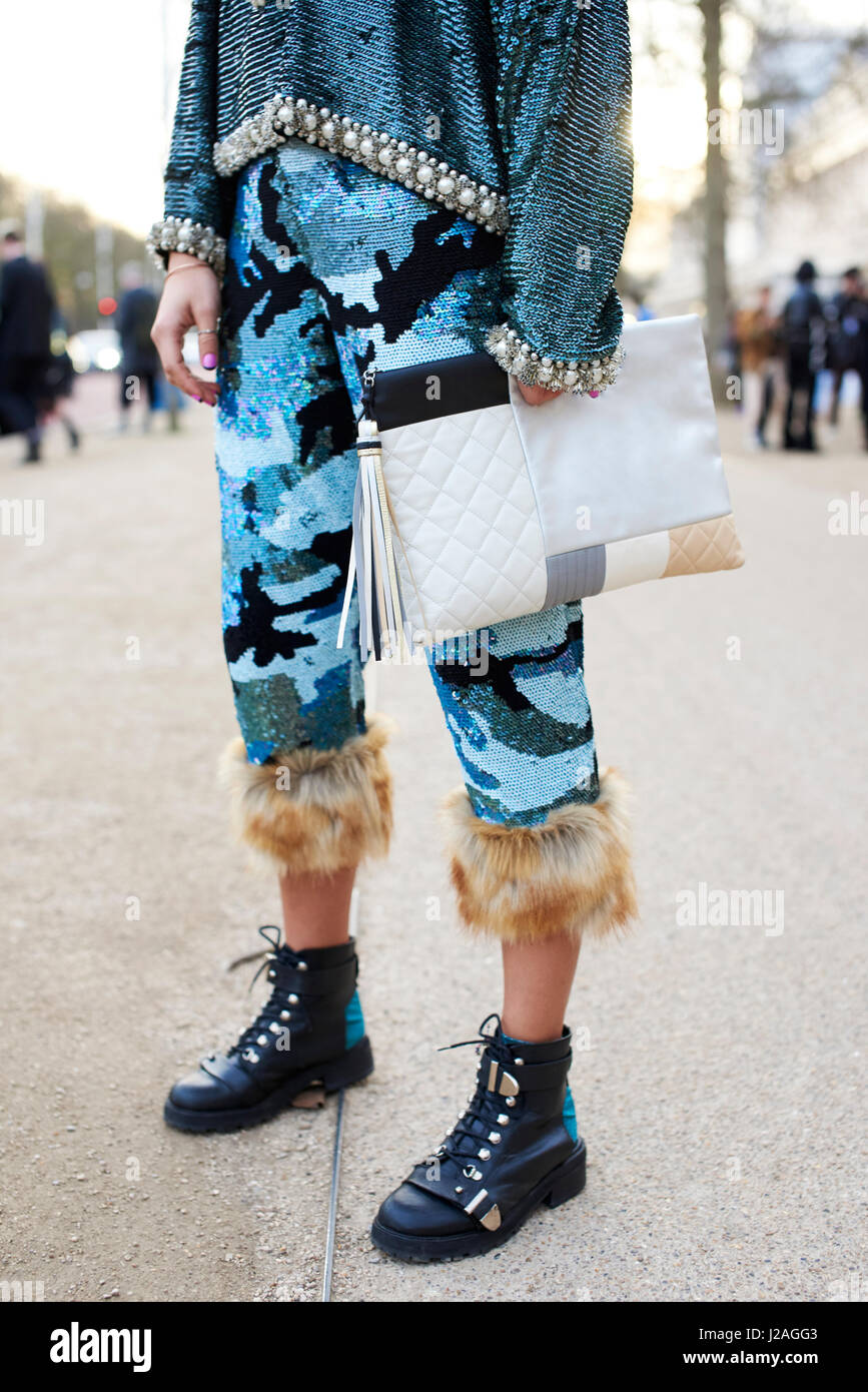 LONDON - FEBRUARY, 2017: Low section of woman in Ashish trousers and top holding an oversized Chanel clutch handbag - Stock Image