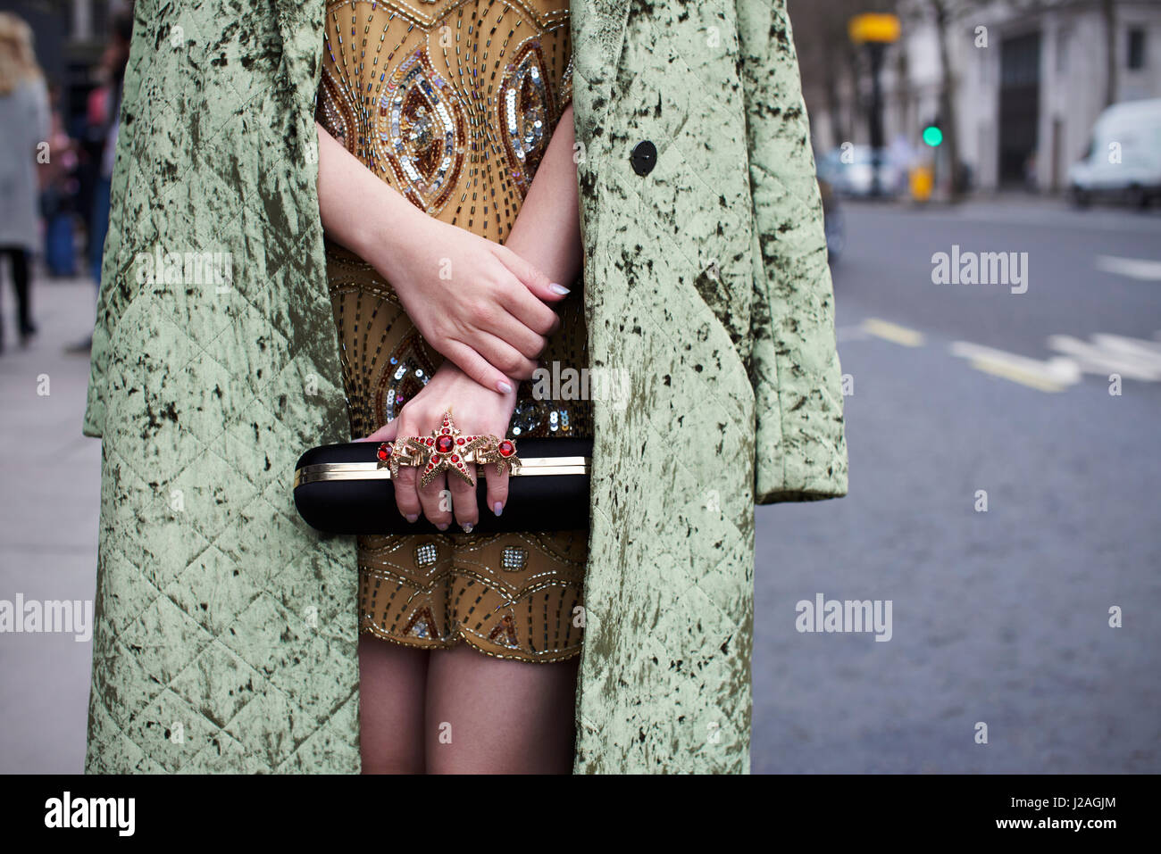 LONDON - FEBRUARY, 2017: Mid section of fashionable woman wearing green crushed velvet coat over a minidress with - Stock Image