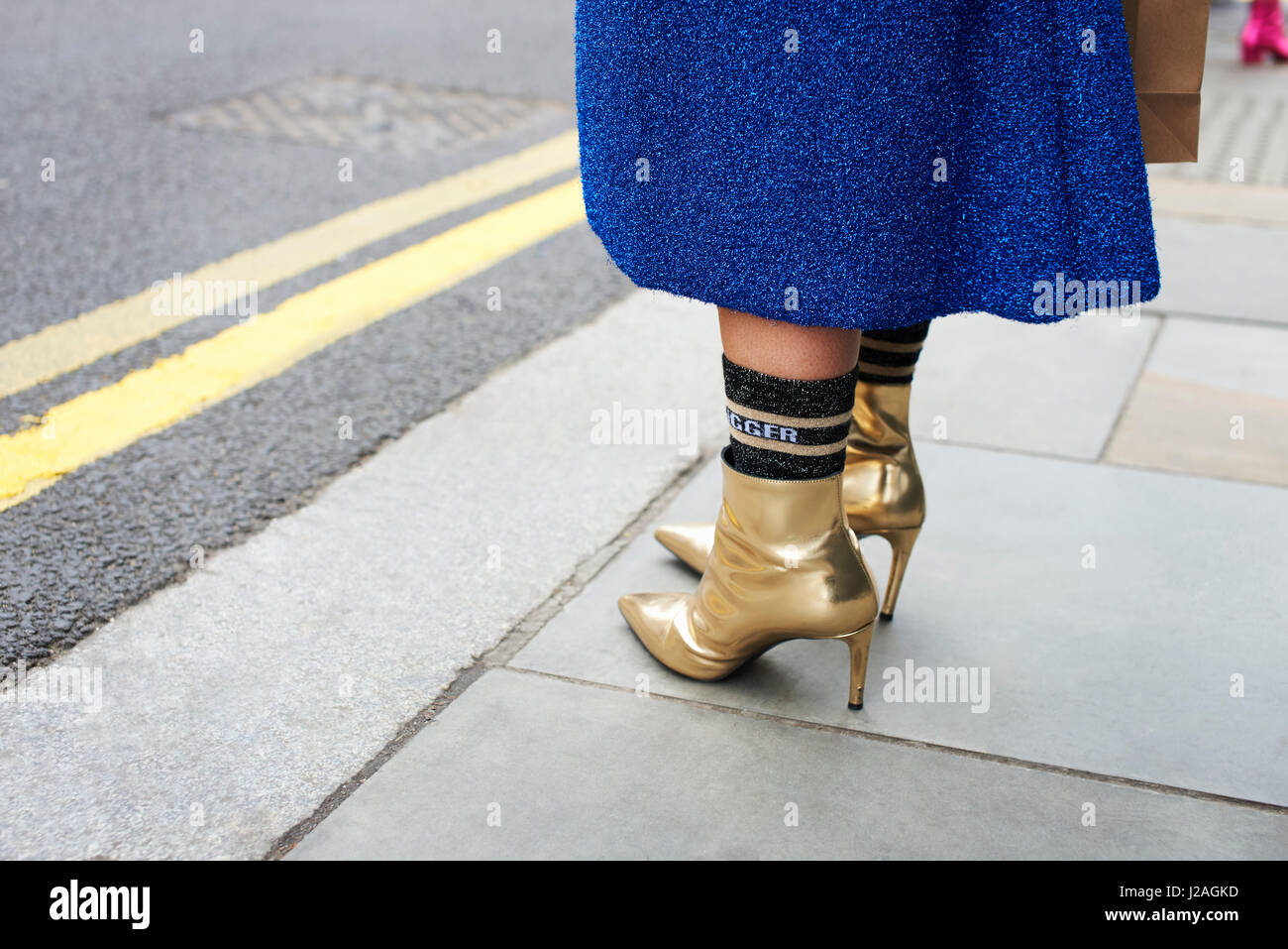 LONDON - FEBRUARY, 2017: Low section of woman wearing blue wool skirt, socks and gold ankle boots standing in the - Stock Image