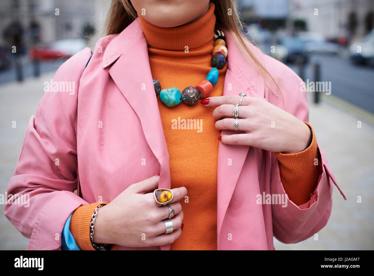 LONDON - FEBRUARY, 2017: Mid section of woman wearing pink coat and orange sweater with chunky stone necklace and - Stock Image