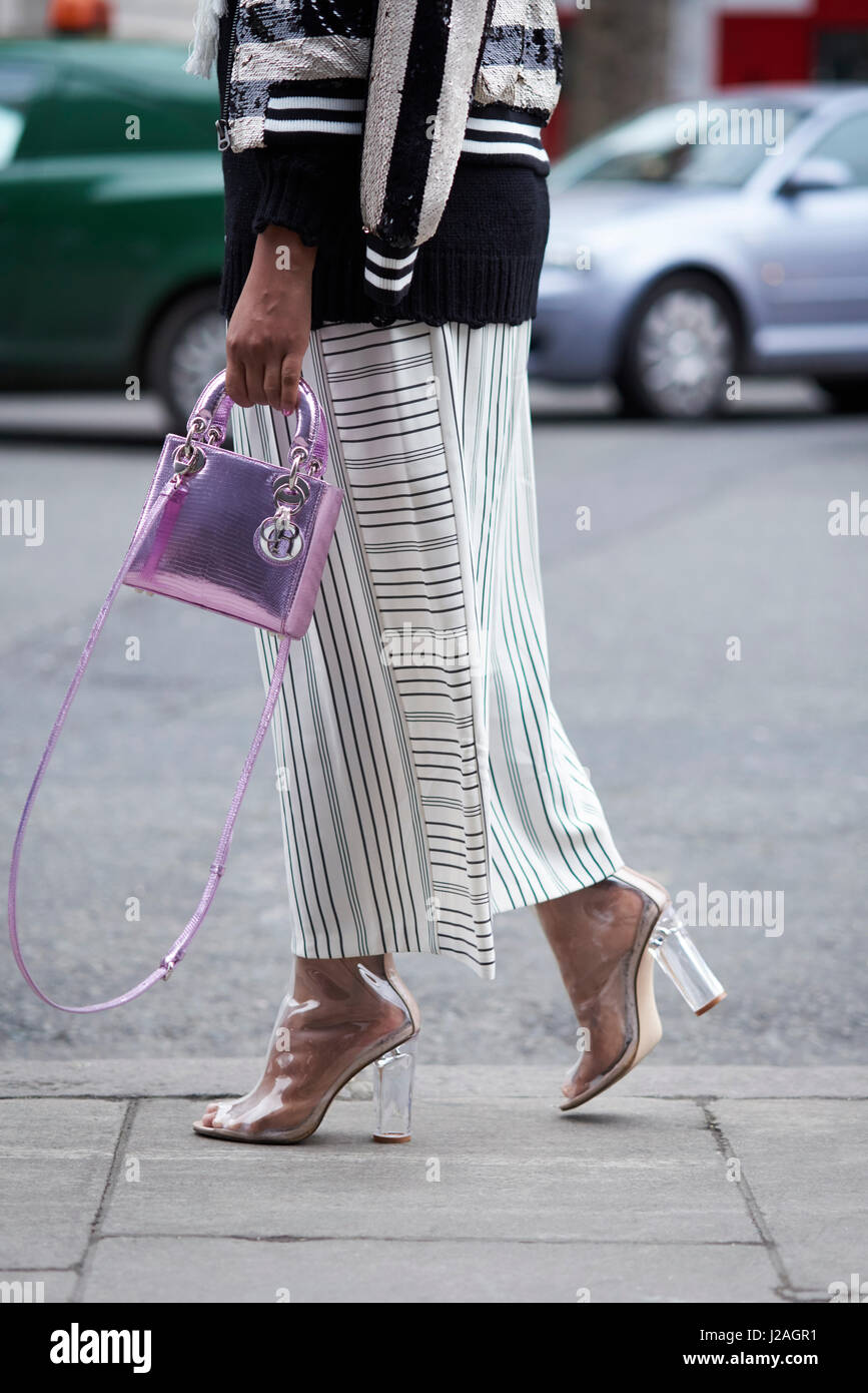 LONDON - FEBRUARY, 2017: Low section of woman walking in a street wearing wide striped trousers and transparent - Stock Image